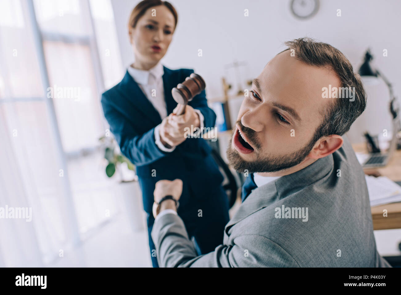 selective focus of lawyer pretending to hit colleague with gavel in hands in office - Stock Image
