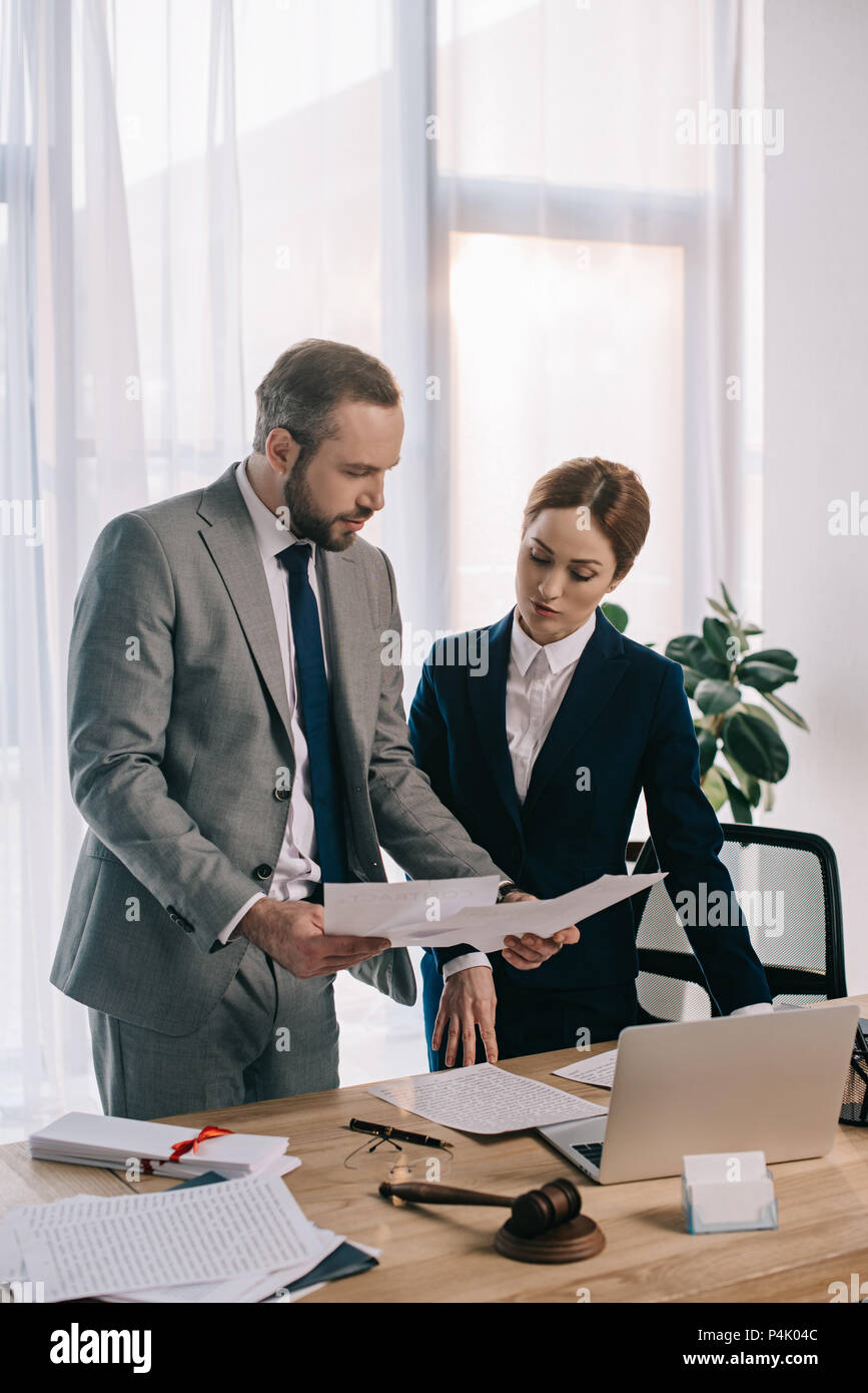 lawyers in suits working together on project at workplace with gavel and laptop in office - Stock Image