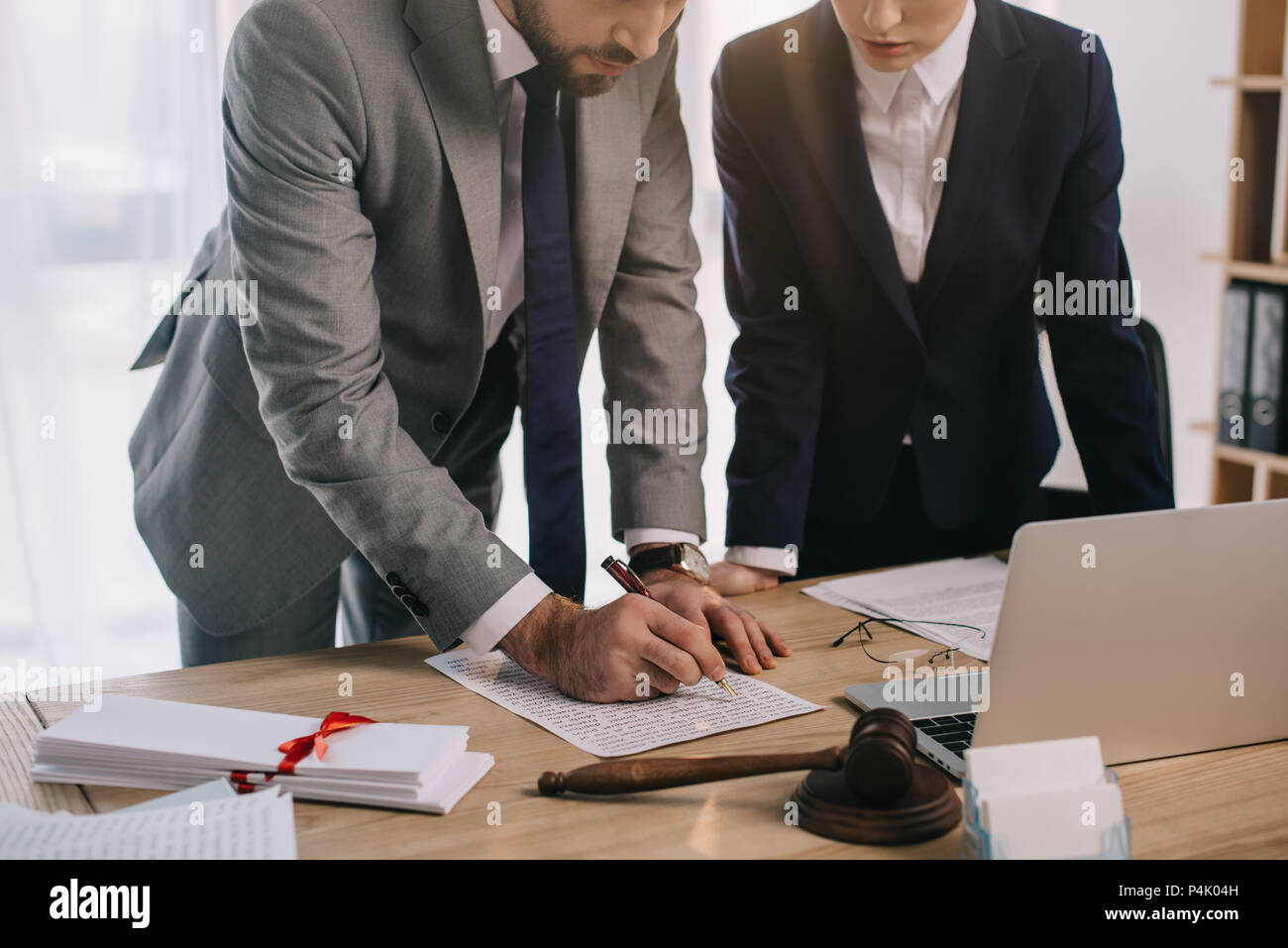 cropped shot of lawyers in suits working together on project at workplace with gavel and laptop in office - Stock Image