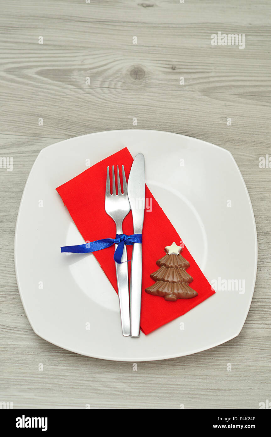 a simple place setting for christmas consisting of a plate, fork, knife,  red napkin and a chocolate shape christmas tree