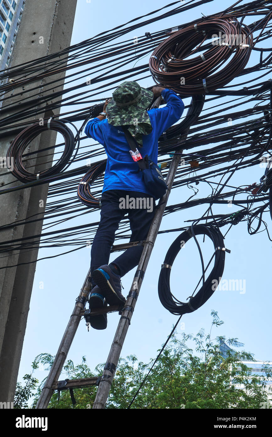 Worker on ladder working on overhead cables and wires - Stock Image