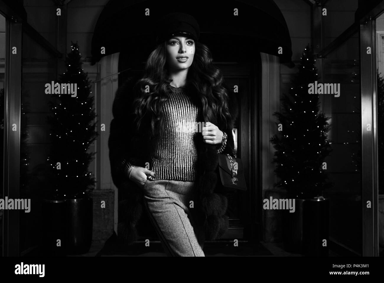 Gorgeous young woman with long brunette hair dressed in gray jumper, trousers and luxurious fur coat, holding handbag, posing on red carpet against bu - Stock Image