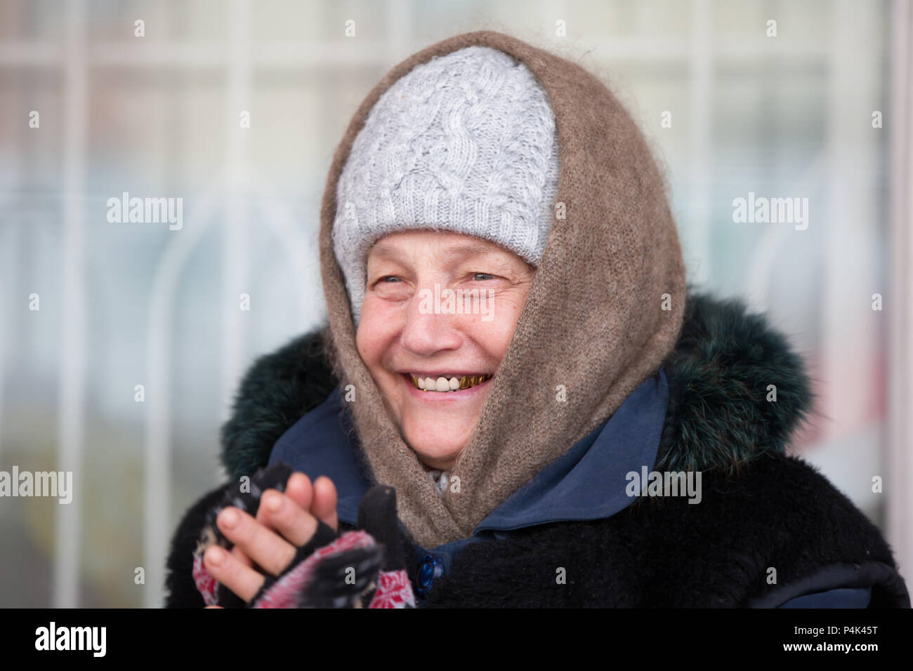 Belarus, Gomel, January 13, 2017. Central market., Shopping arcades. Portrait of a woman in a downy shawl with gold teeth. The old Russian poor woman - Stock Image