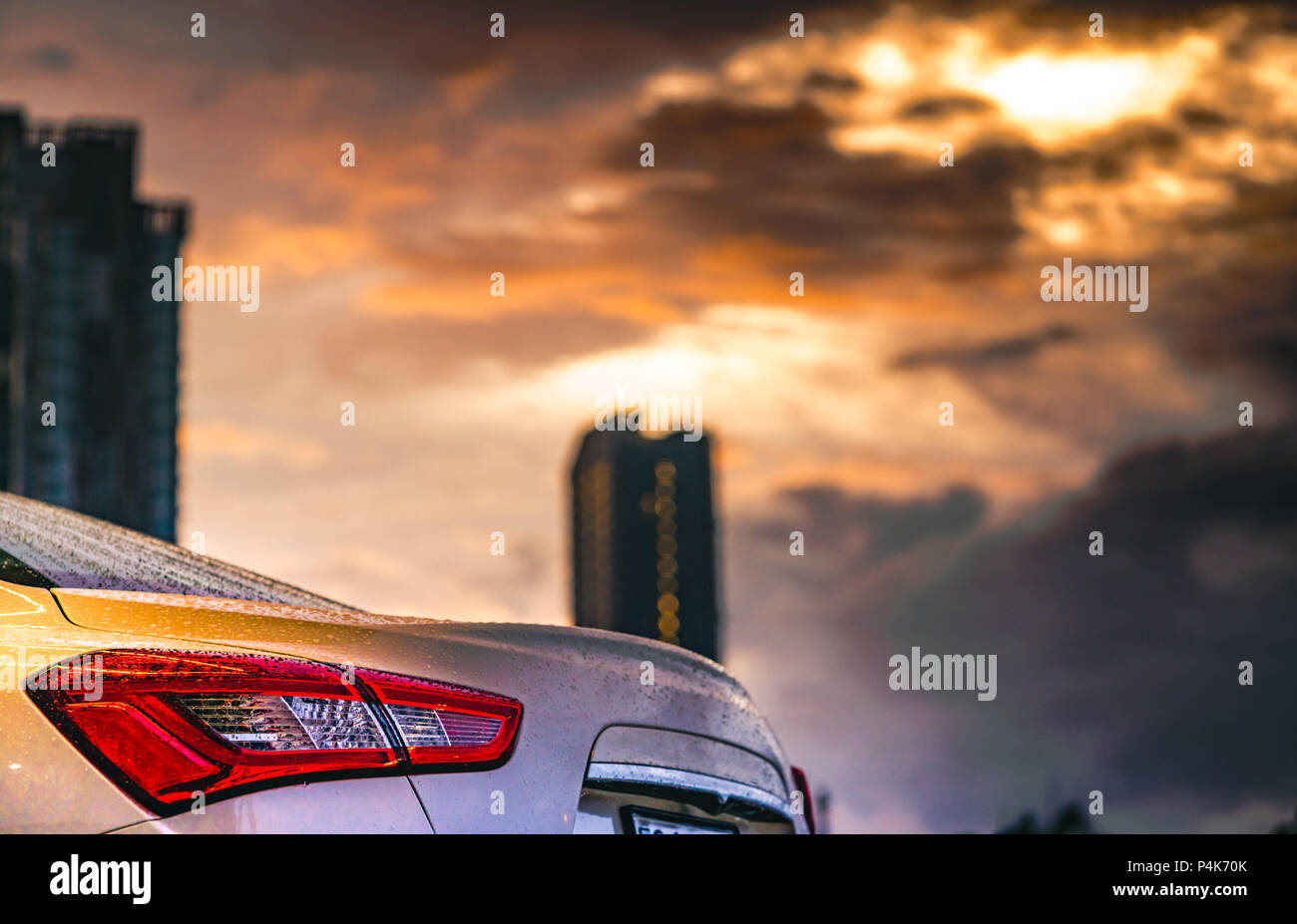 Rear view of car parked in the city near high building after rain with grey and orange sky and clouds and have water droplet on surface of car. Hybrid - Stock Image