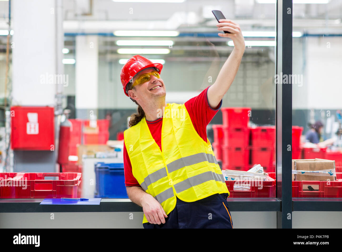 Worker in reflective west with red helmet taking selfie in a factory - Stock Image