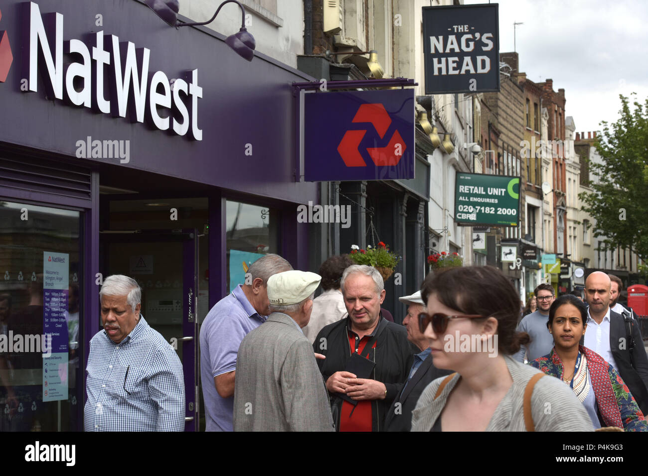 People walk past the bank branch of NatWest on Upper Street, Islington, North London - Stock Image
