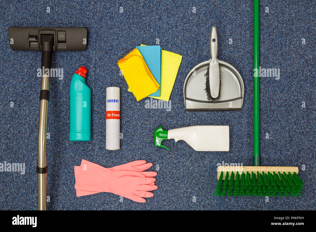 A flat lay arrangement of cleaning equipment on a blue office carpat background. - Stock Image
