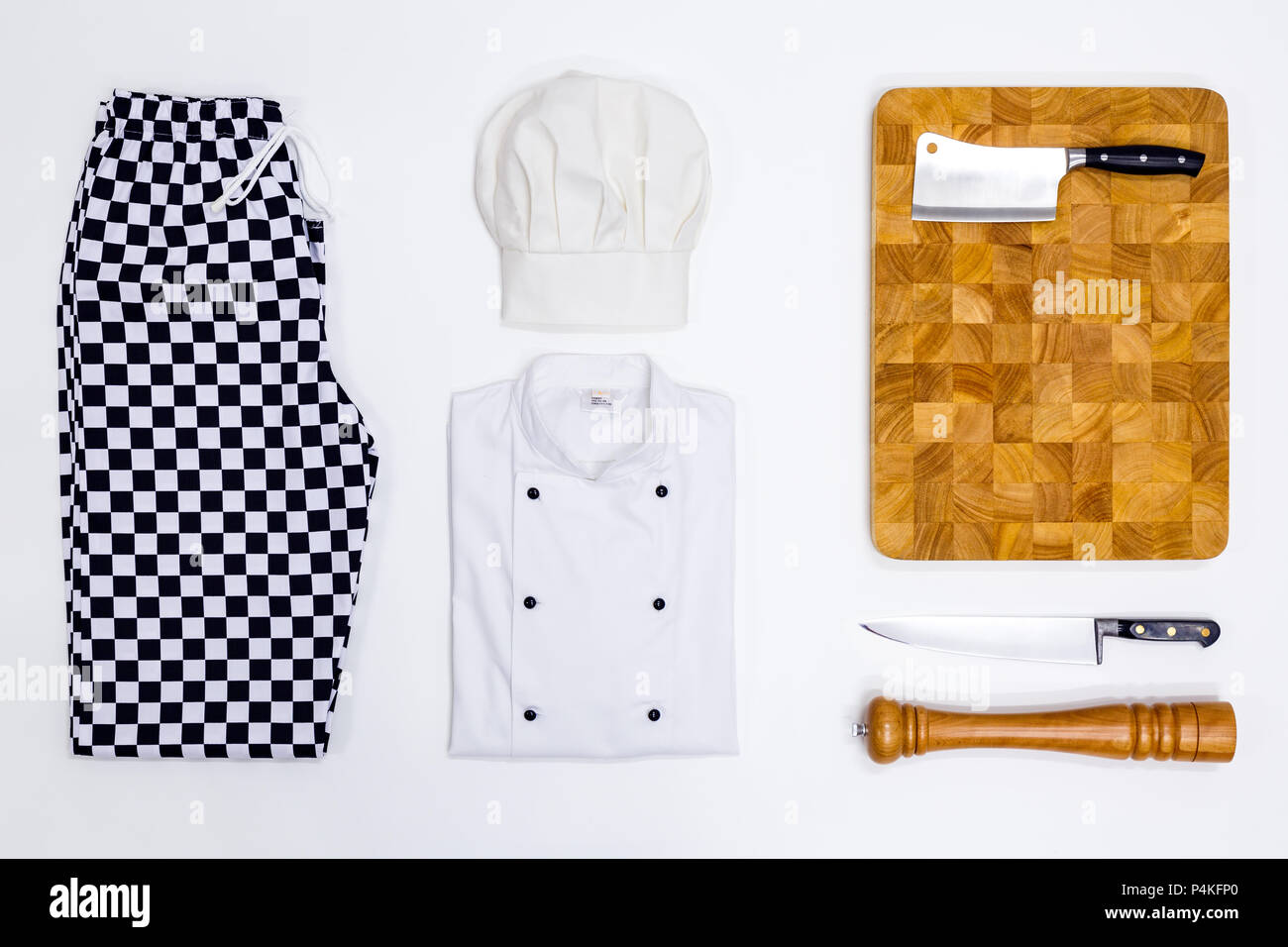 A flat lay arrangement of Chef whites uniform and equipment. - Stock Image