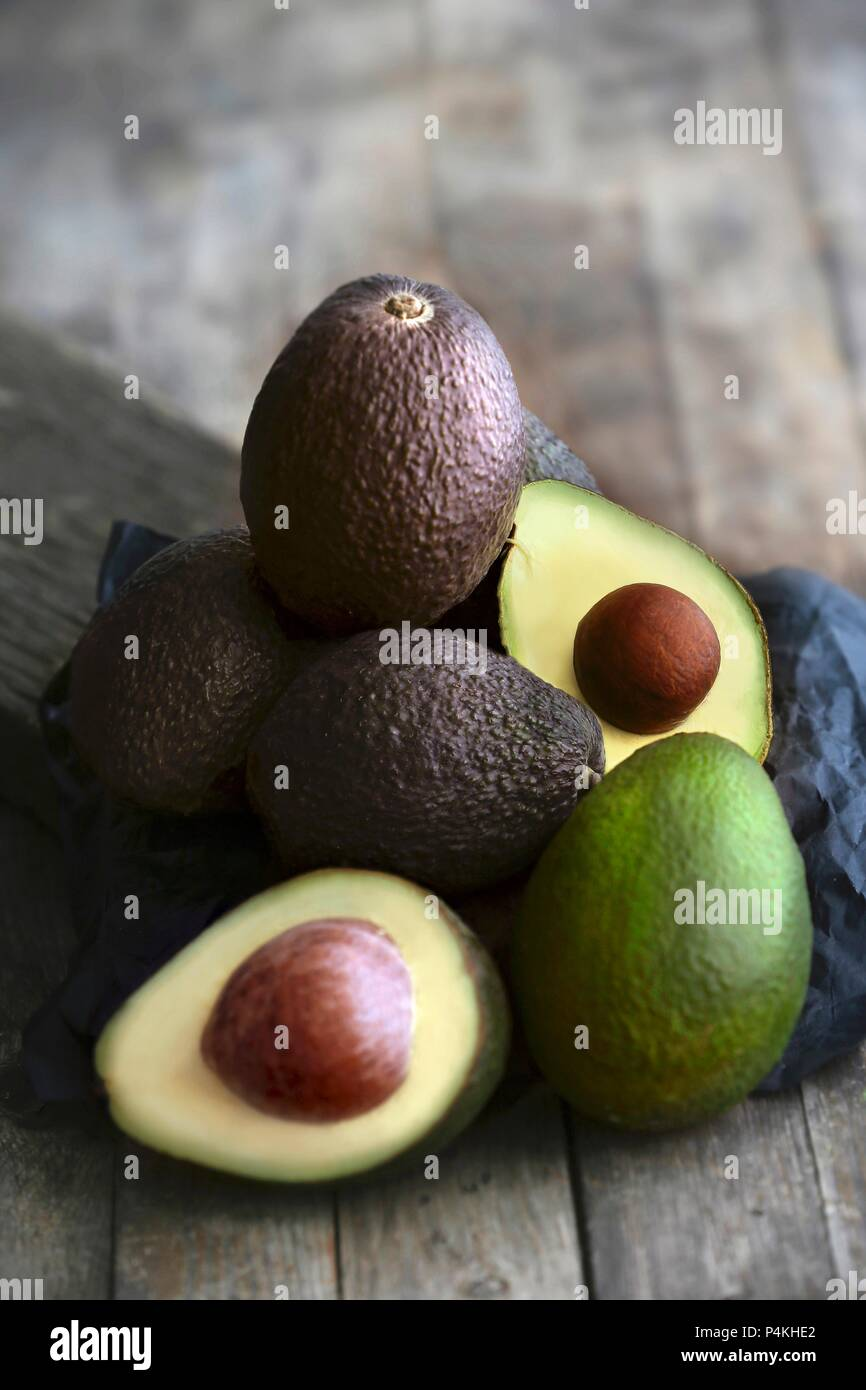 A stack of avocados on a dark wooden surface - Stock Image