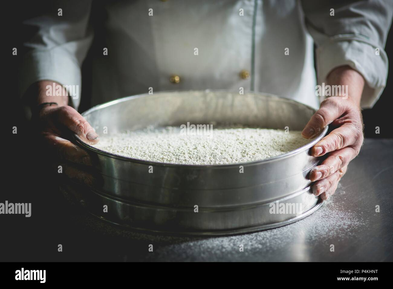 A confectioner with a large sieve of icing sugar - Stock Image