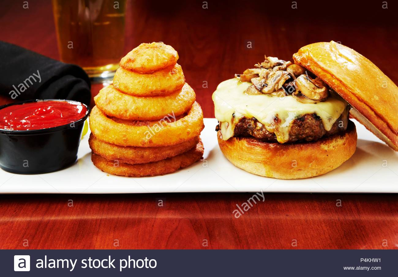 A cheeseburger with mushrooms served with onion rings and ketchup - Stock Image