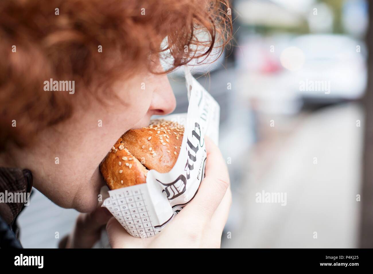 A red-haired teenager biting into a hamburger Stock Photo
