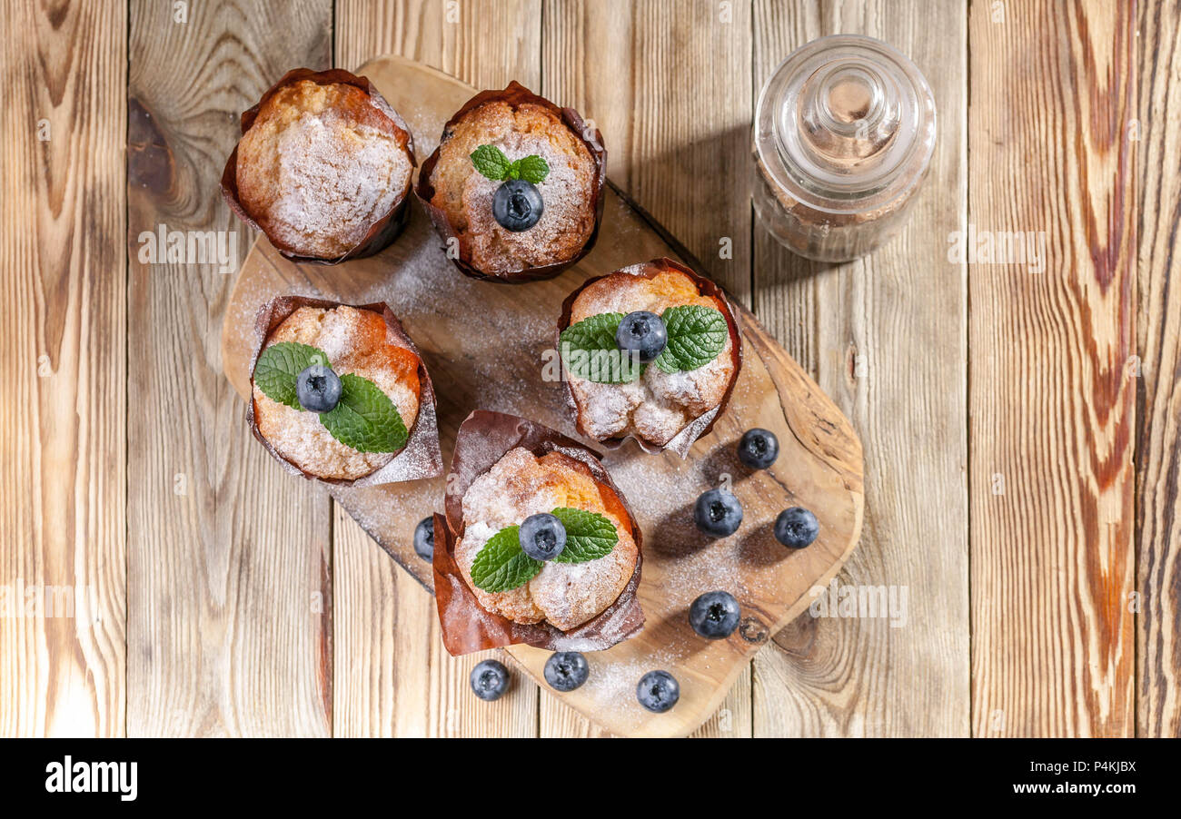 Muffins with blueberries on a wooden background. homemade baking. Top view - Stock Image