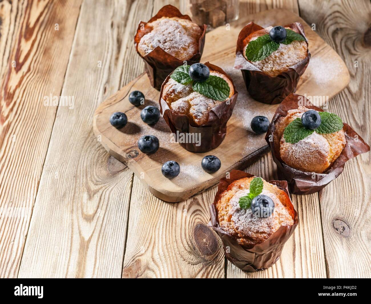 Muffins with blueberries on a wooden background. homemade baking - Stock Image