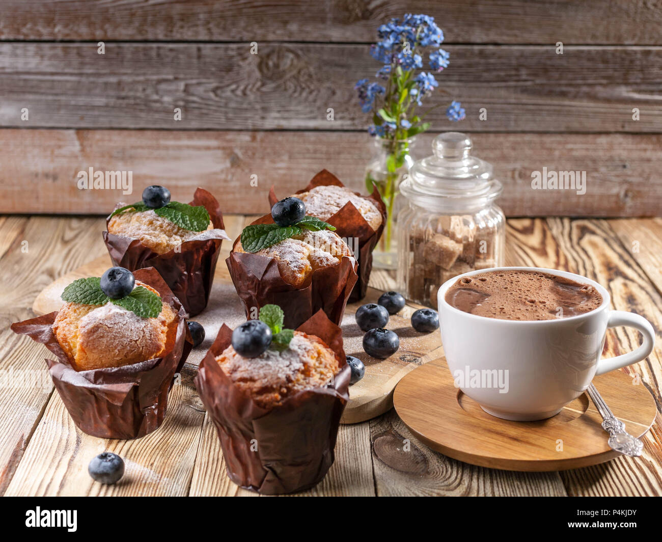 Muffins with blueberries and a cup of hot chocolate on a wooden background. homemade baking - Stock Image