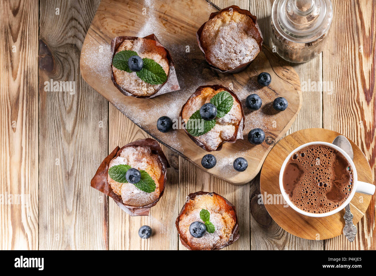 Muffins with blueberries and a cup of hot chocolate on a wooden background. homemade baking. Top view - Stock Image