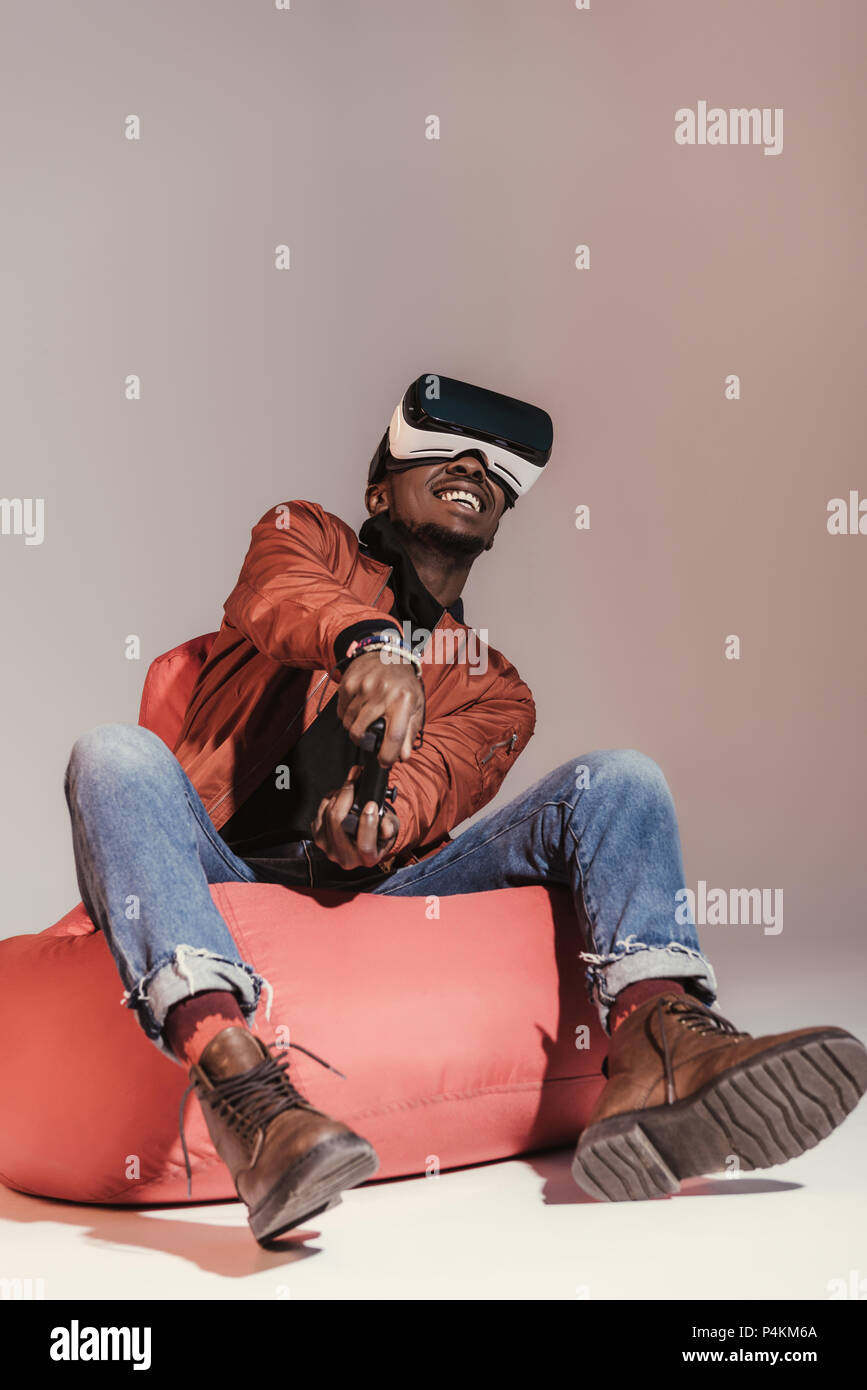 african american man in virtual reality headset playing with joystick while sitting on bean bag chair - Stock Image