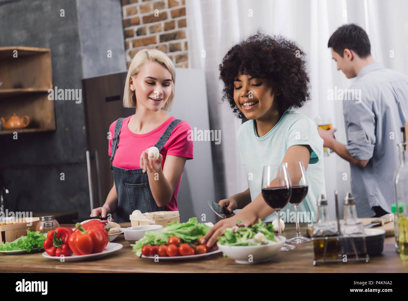 smiling multiethnic girls cooking in kitchen - Stock Image