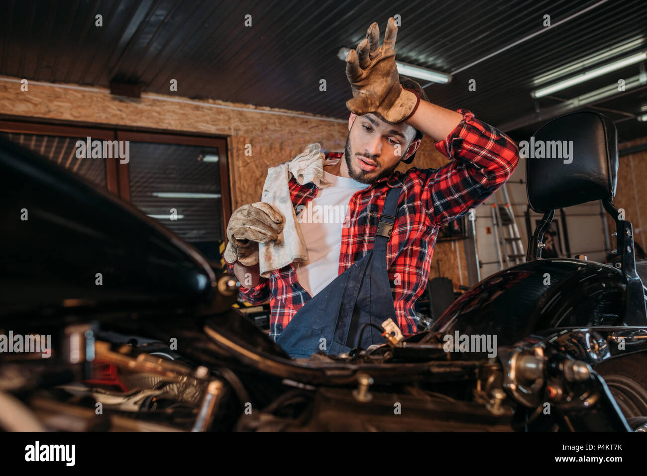 exhausted bike repair station worker wiping sweat from forehead after work at garage - Stock Image