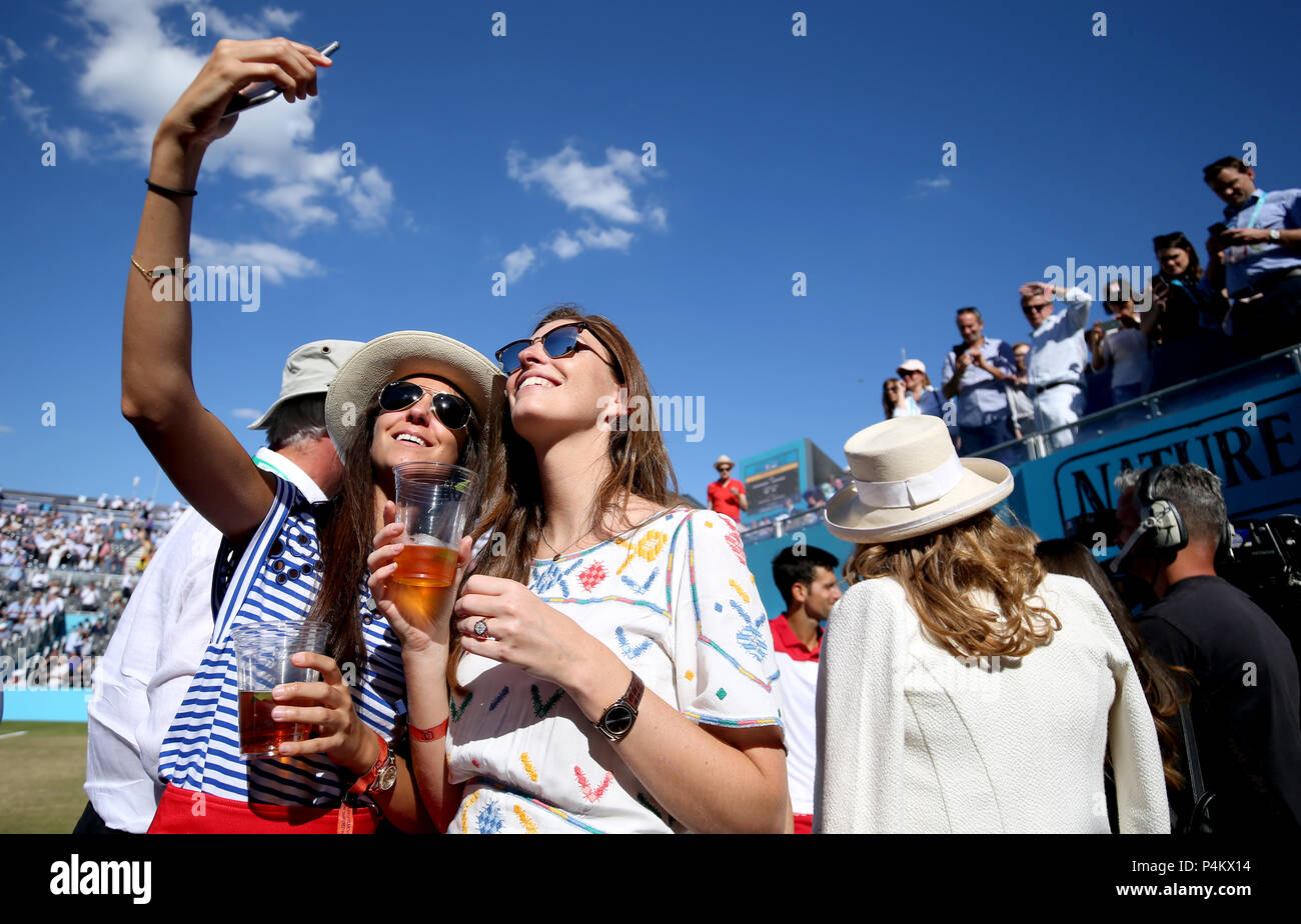 Spectators take a selfie as Novak Djokovic gives a TV interview after winning his match during day five of the Fever-Tree Championship at the Queen's Club, London. - Stock Image