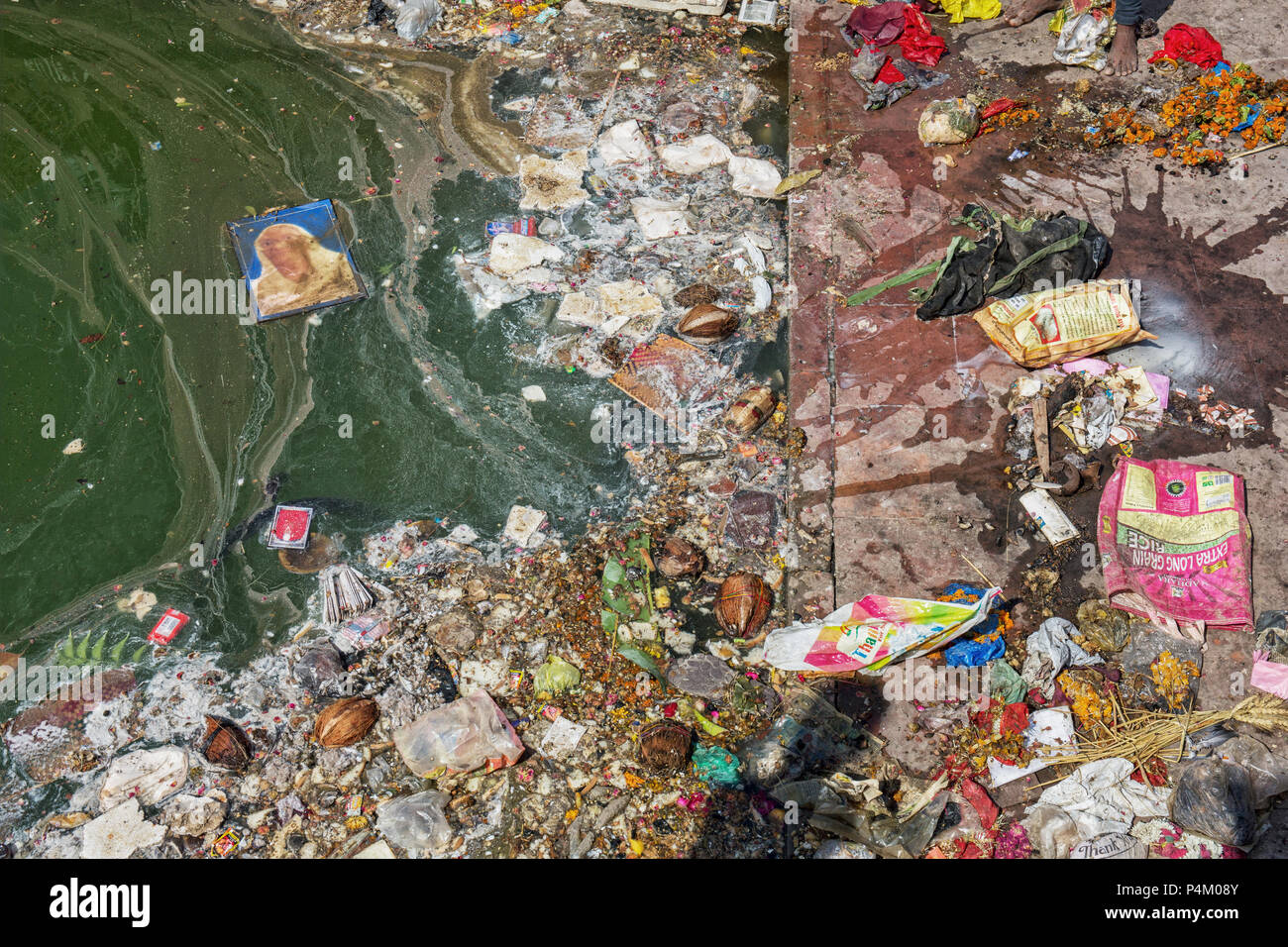 Pollution on the beach of tropical sea. Plastic garbage, foam, wood and dirty waste on beach in summer day - Stock Image