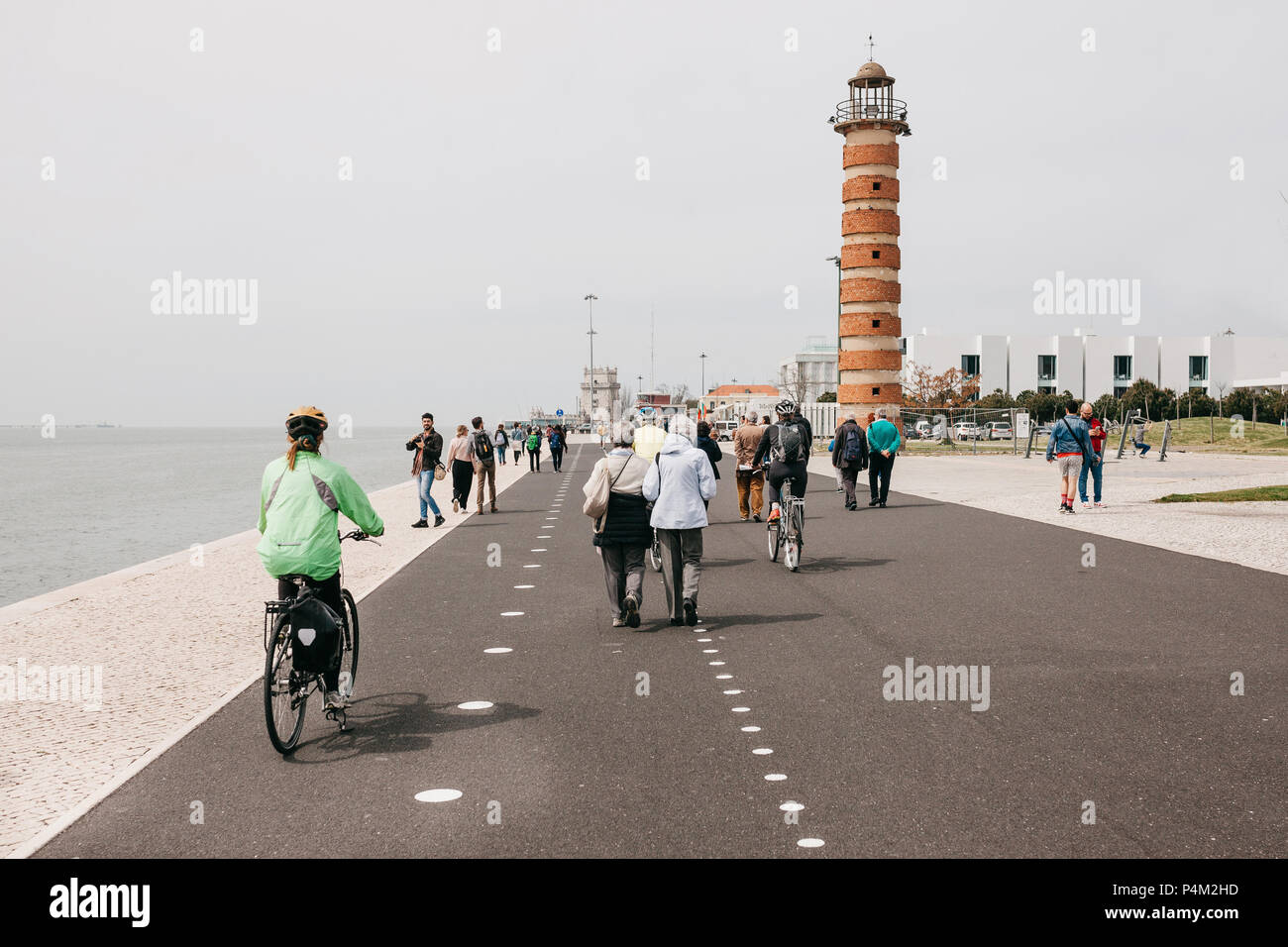 Lisbon, June 18, 2018: People stroll along the promenade in the Belem area. Some people ride bicycles. Ordinary city life Stock Photo