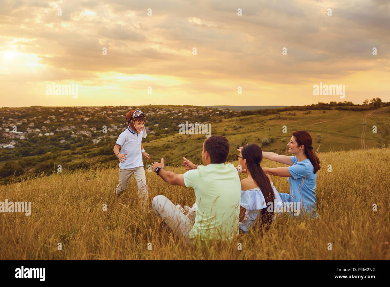 Happy family having fun playing on grass in nature. - Stock Image