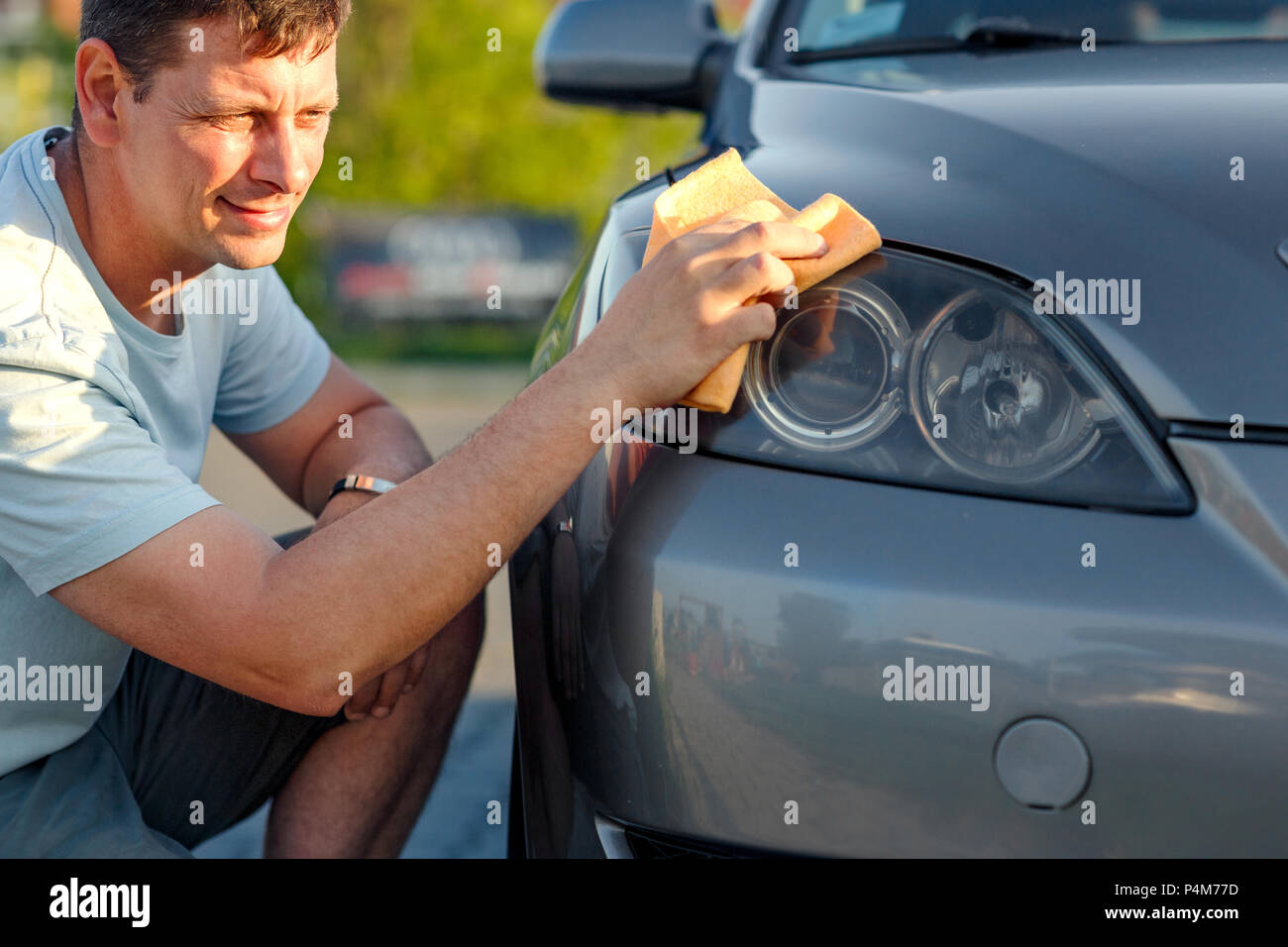 Giving the car a good polish - close up of man cleaning car with microfiber cloth, car detailing Stock Photo