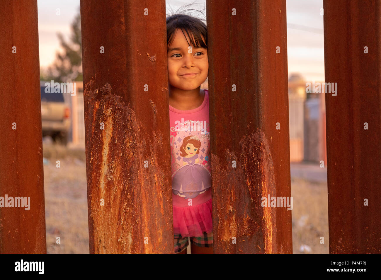 Children play on the Mexican side of the US Mexican border wall, Trump wall, Nogales, USA, Mexico. - Stock Image