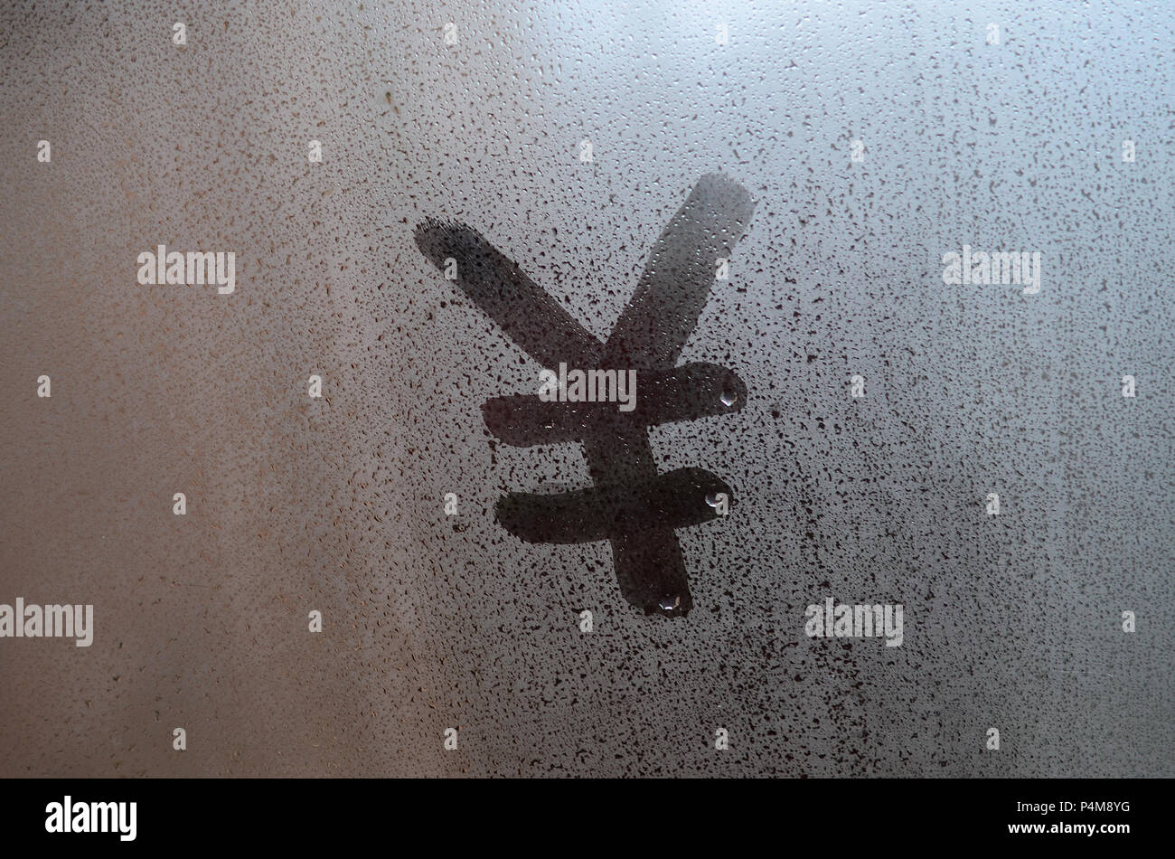 Chinese Yen Symbol is written with a finger on the surface of the misted glass . - Stock Image