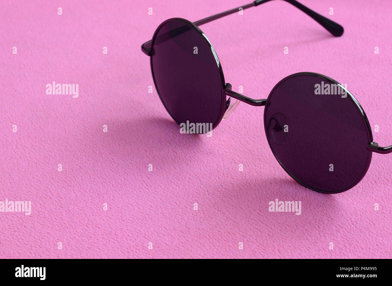 1ca55fc049f Stylish black sunglasses with round glasses lies on a blanket made of soft  and fluffy light