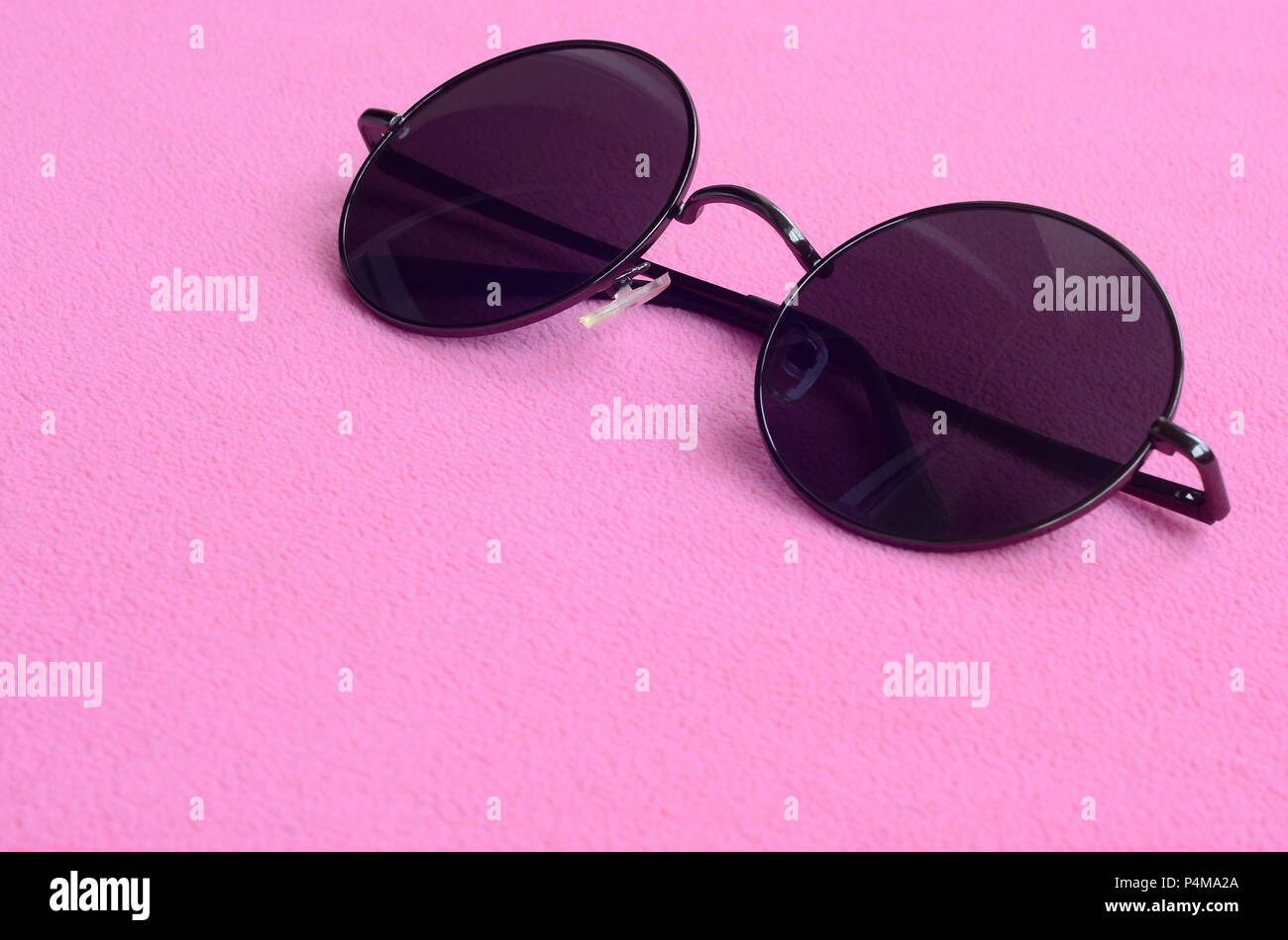 de2606bb5d93 Stylish black sunglasses with round glasses lies on a blanket made of soft  and fluffy light pink fleece fabric. Fashionable background picture in fema