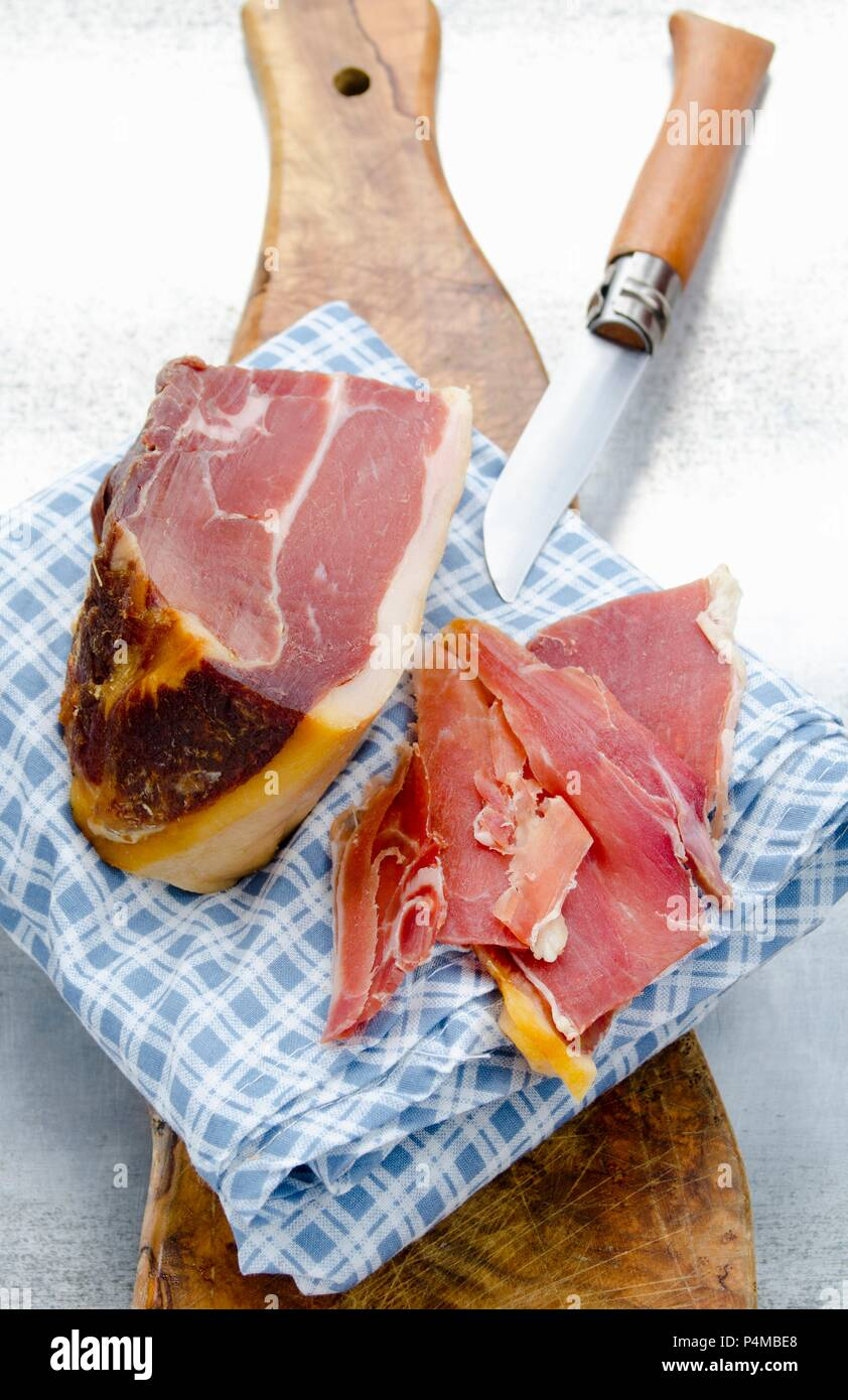 Spanish Serrano ham, a large piece and slices - Stock Image