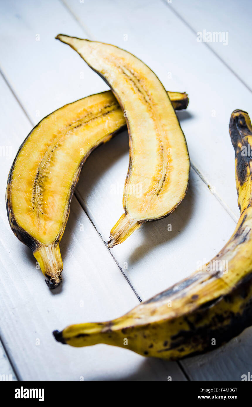 Plantain cut in half and whole on a white wooden background - Stock Image