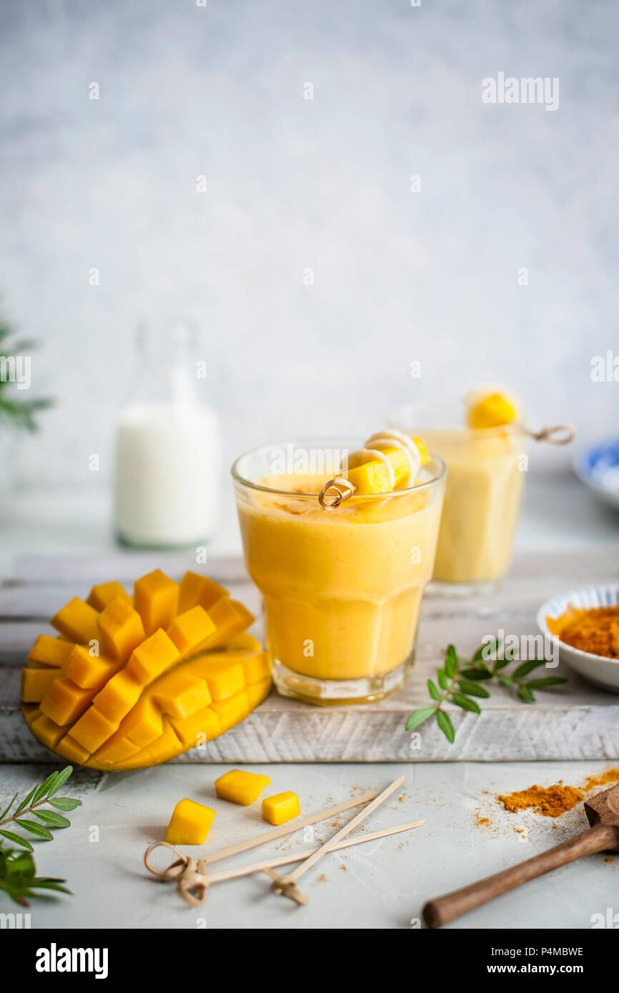 Mango lassi with turmeric and honey, fresh mango on a side - Stock Image