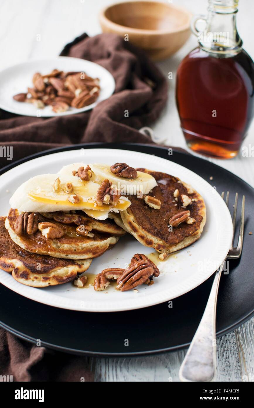 Pancakes with bananas, maple syrup and pecans - Stock Image