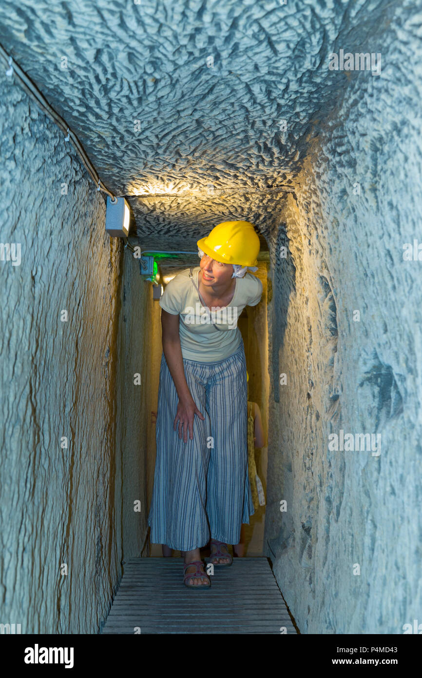 Woman /tourist / female exploring the air raid shelter tunnel / narrow & low tunnels inside / underground at the Malta At War Museum, Malta. (91) - Stock Image