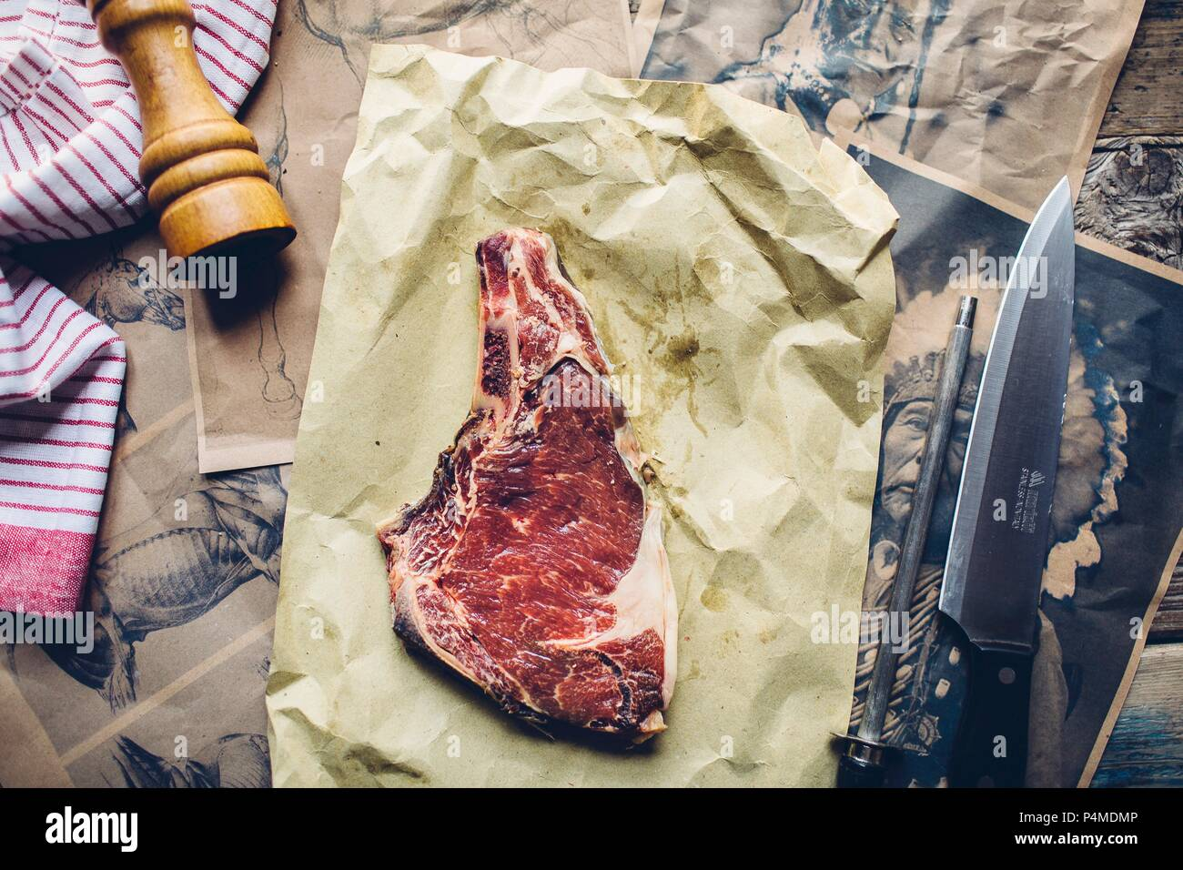 A raw horse steak on baking paper - Stock Image