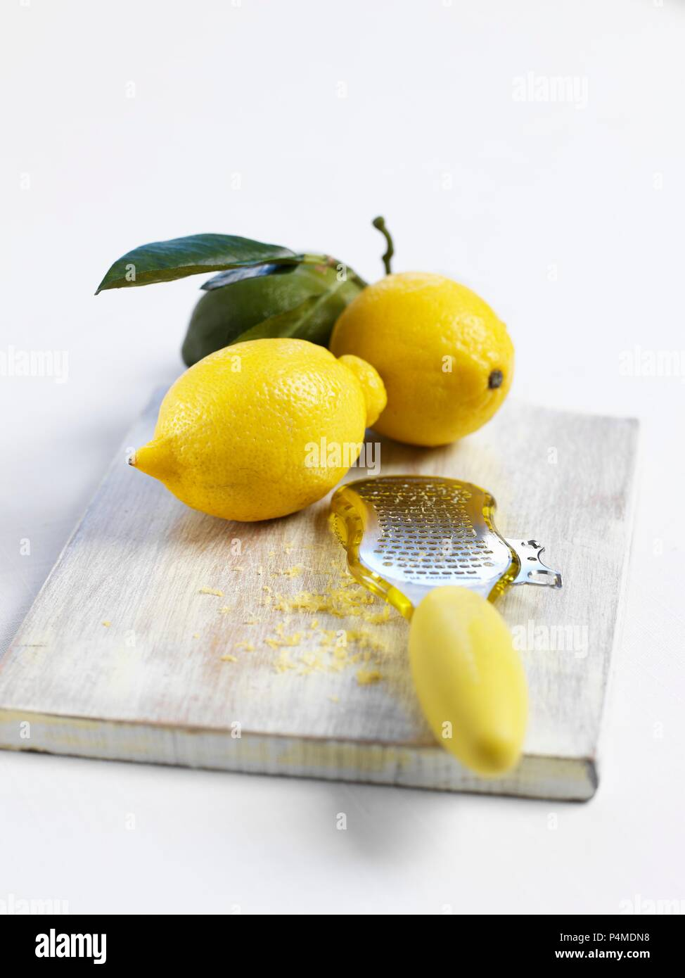 Lemons and a grater with lemon zest - Stock Image
