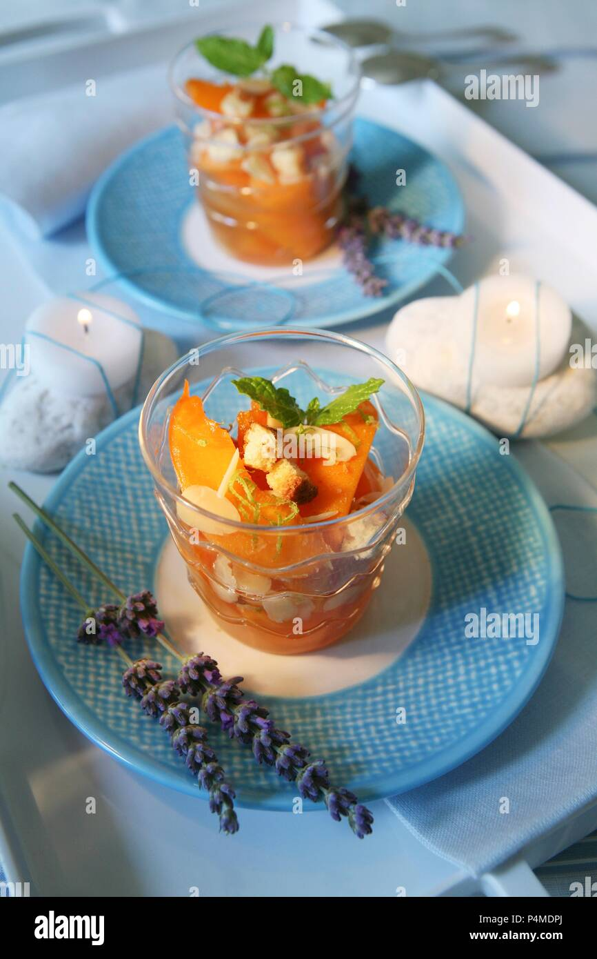 Vin Santo peaches with roasted flaked almonds, biscuit and mint leaves - Stock Image