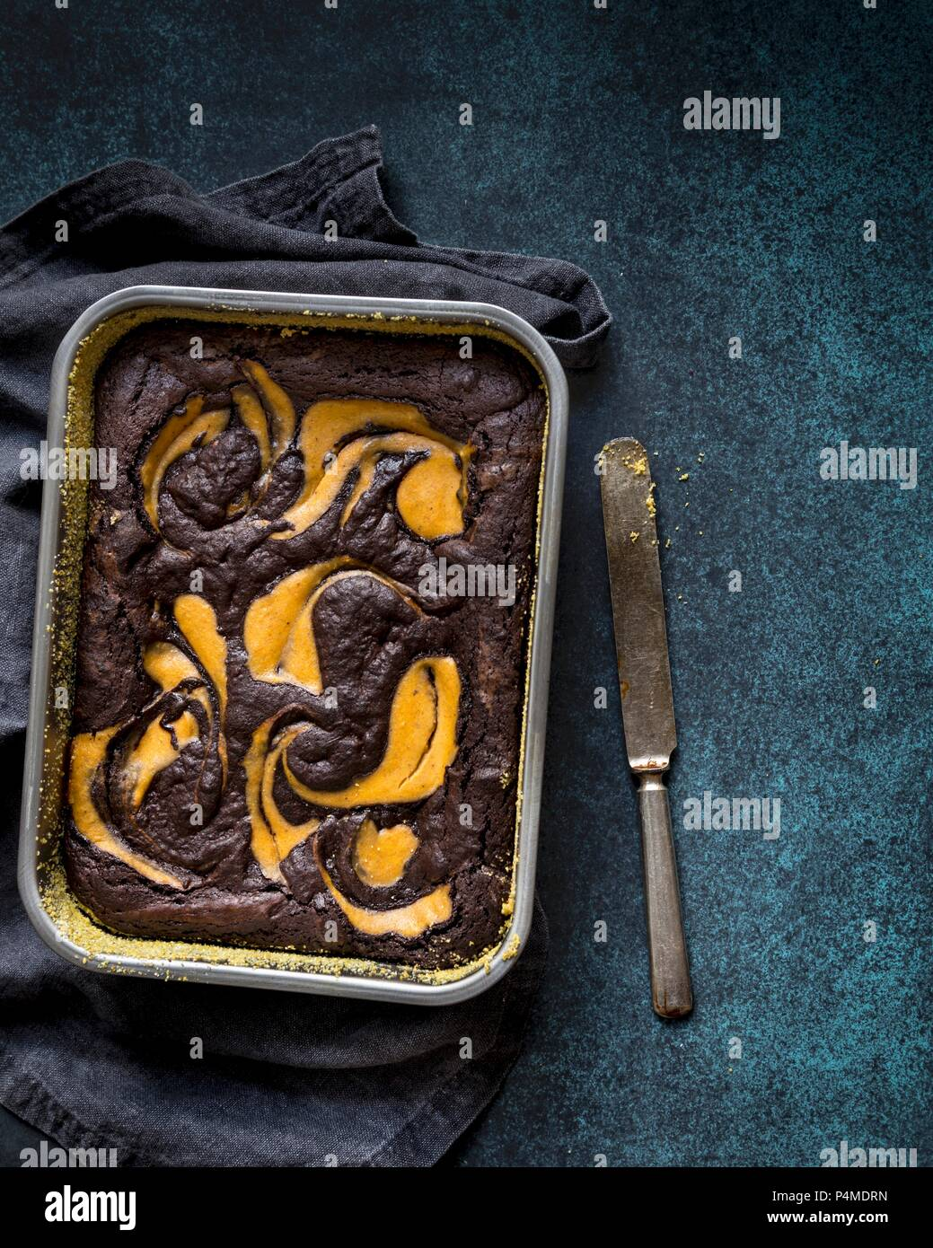 Gluten-free brownie and pumpkin cake in a baking tin - Stock Image