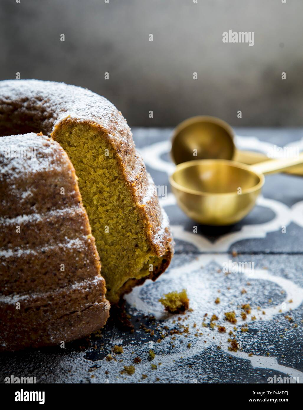 Matcha gugelhupf with icing sugar, cut into pieces - Stock Image