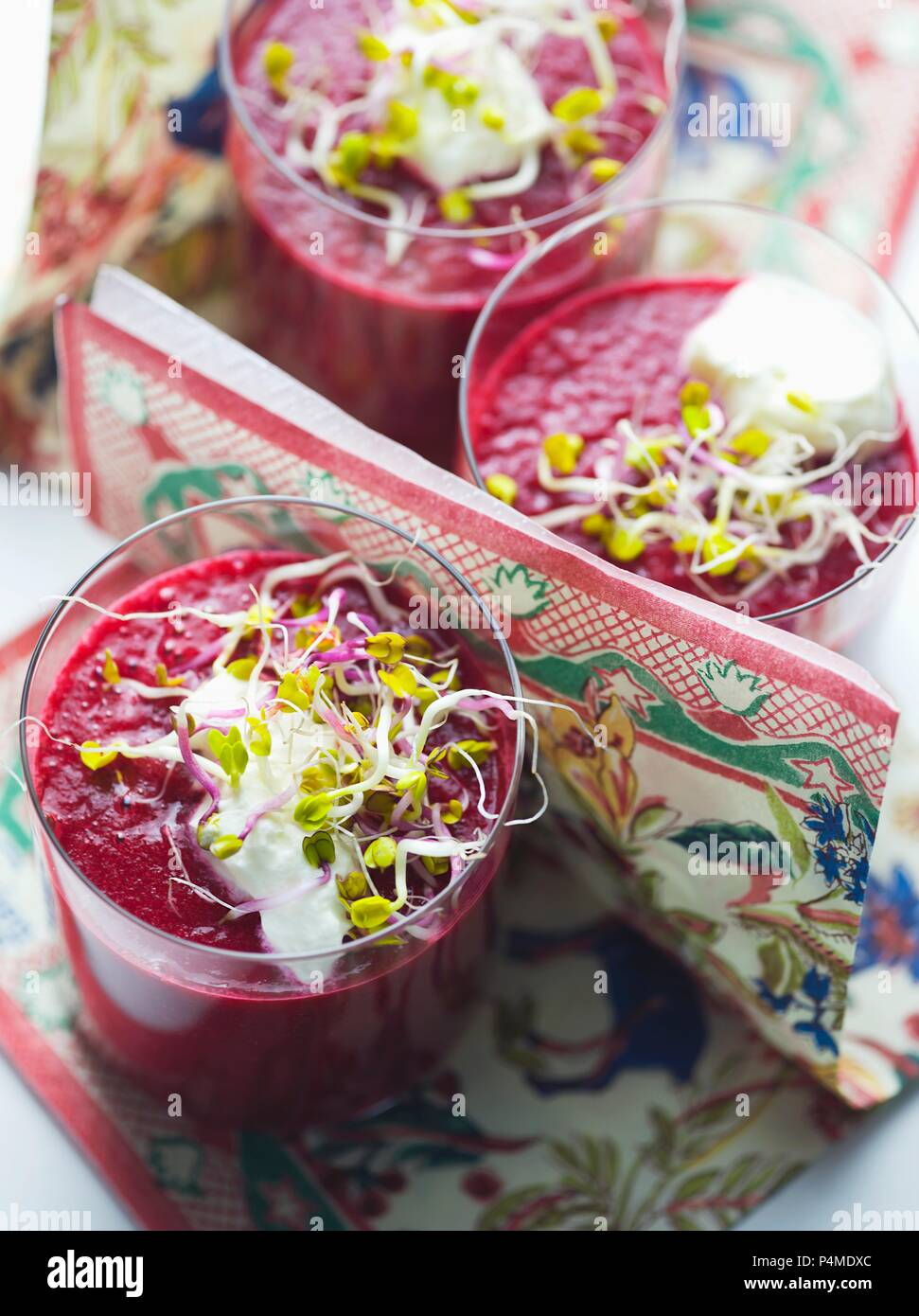 Beetroot juice garnished with shoots and sour cream - Stock Image
