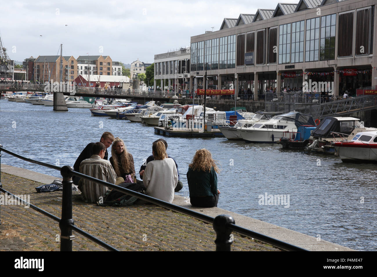 Young people sit together chatting at Broad Quay, Bristol, England. - Stock Image