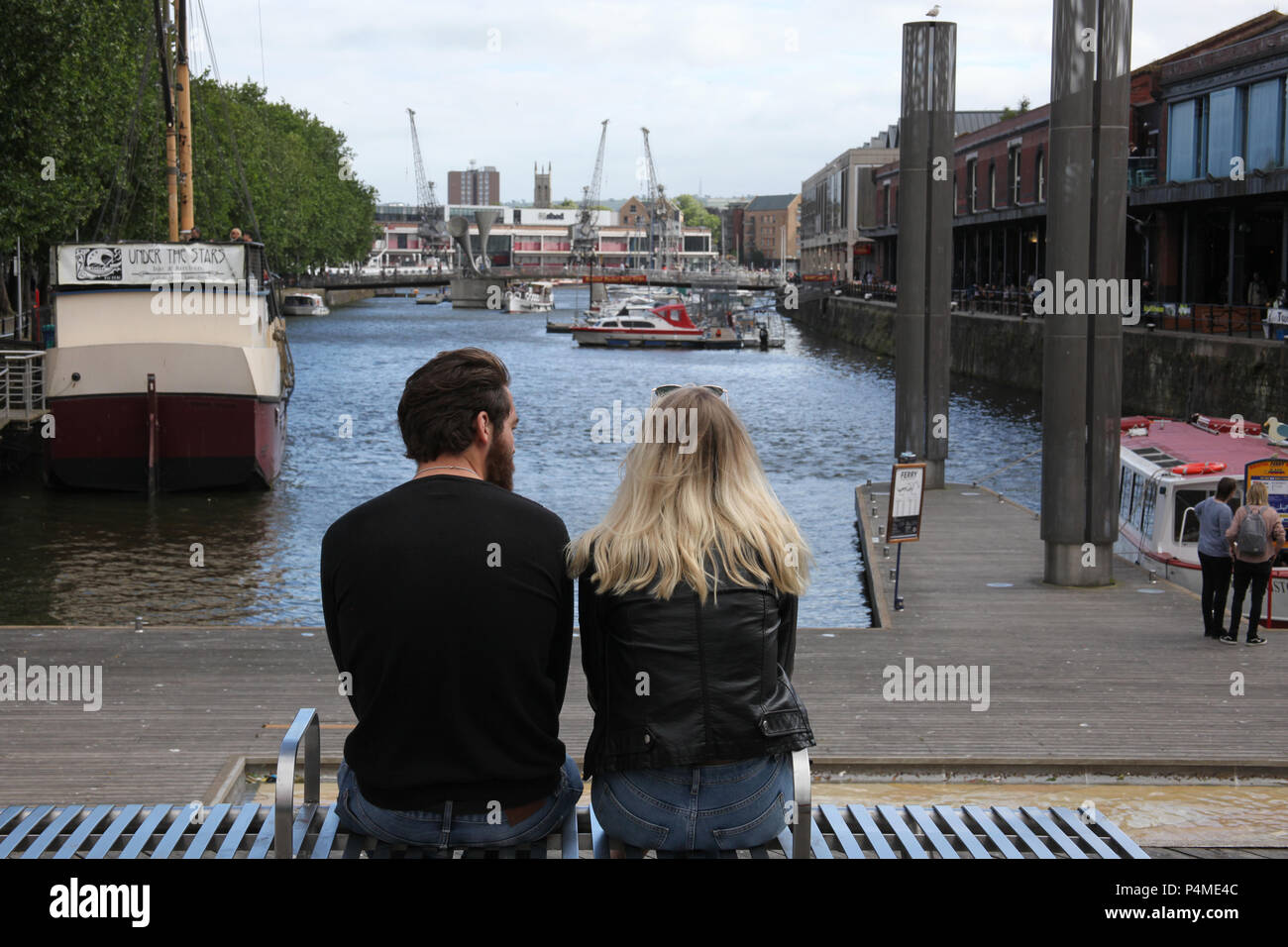 A young couple sit on Broad Quay, Bristol, England. - Stock Image