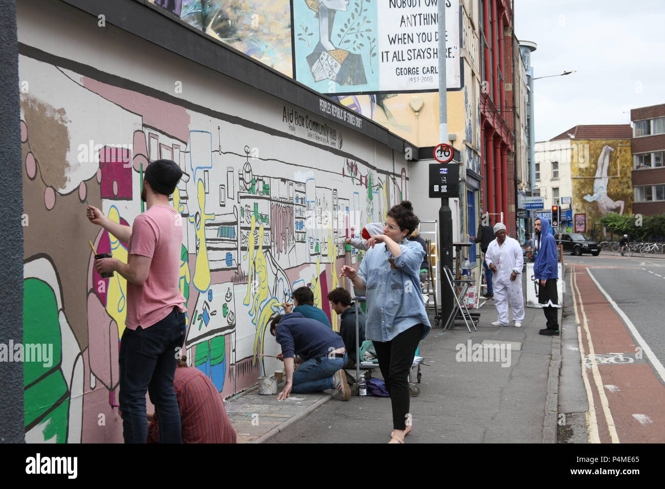 People painting art on city walls in Stokes Croft, Bristol, England. - Stock Image