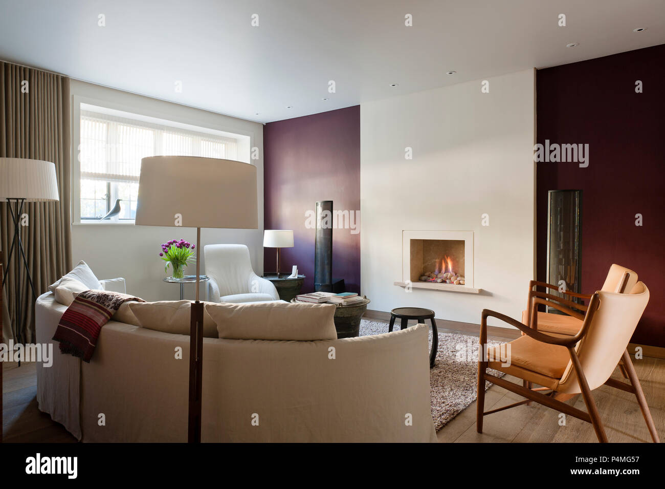 Retro living room with lit fireplace - Stock Image