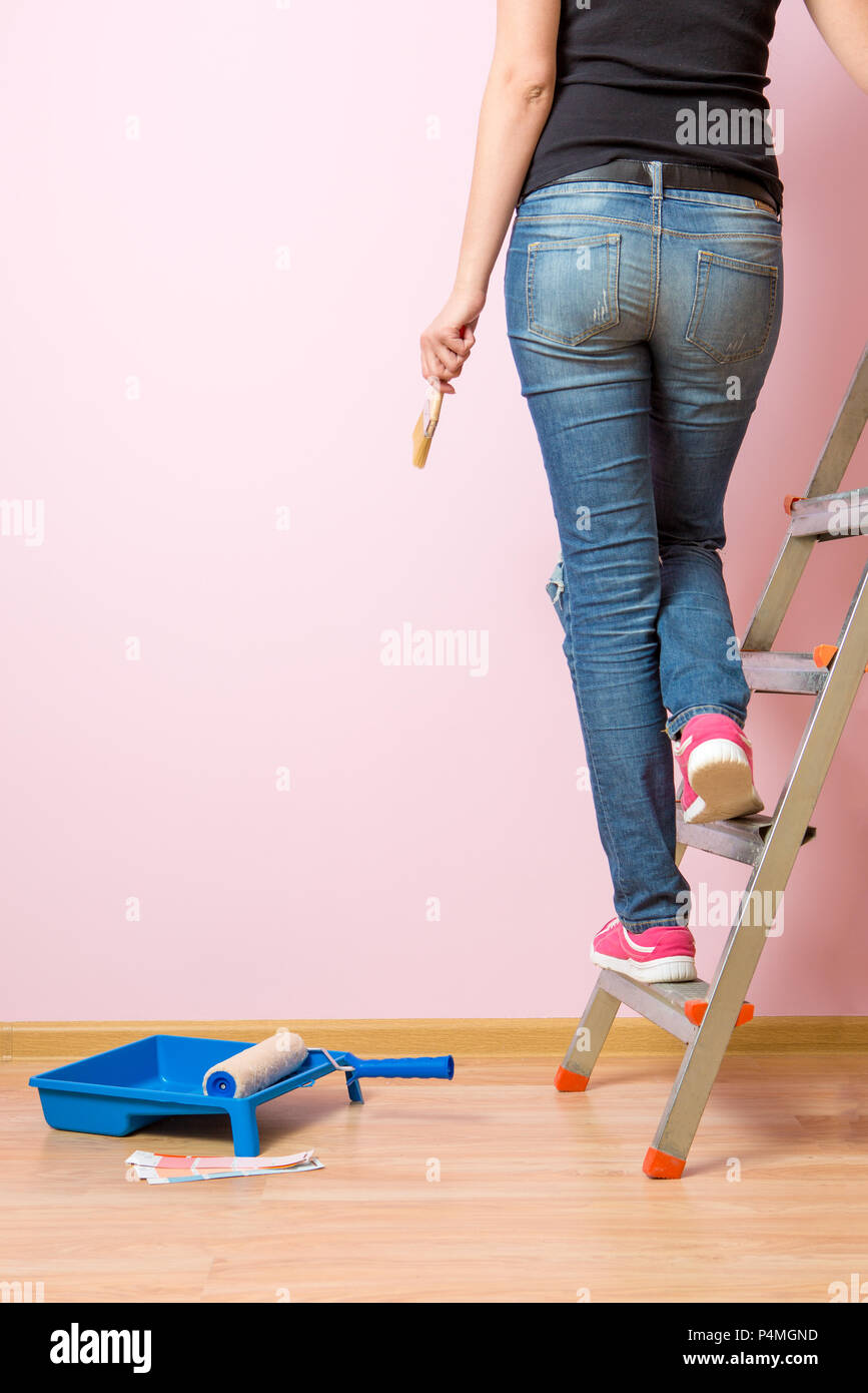 Photo from back of woman with brush standing on stepladder Stock Photo