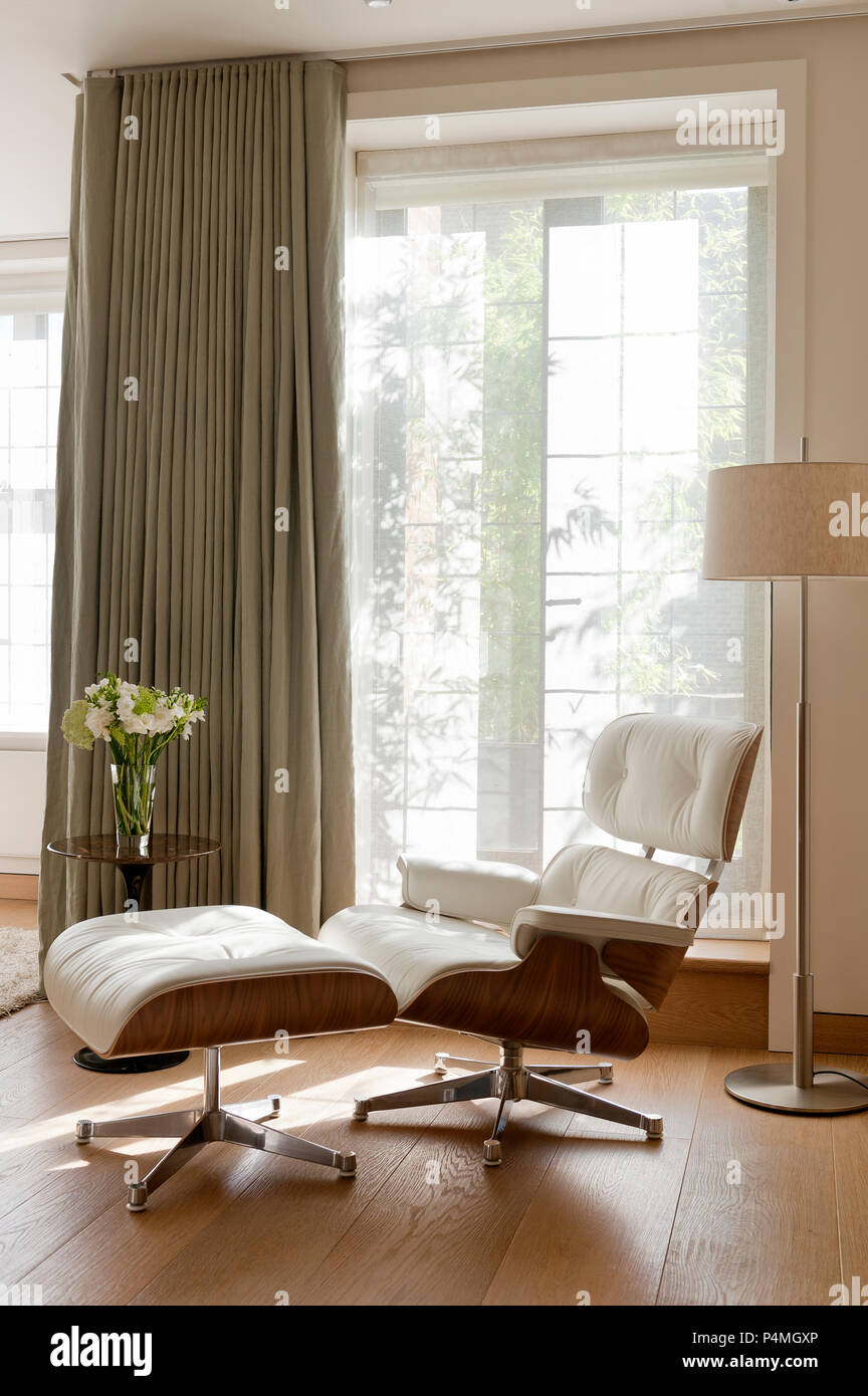 Armchair and flowers by door - Stock Image
