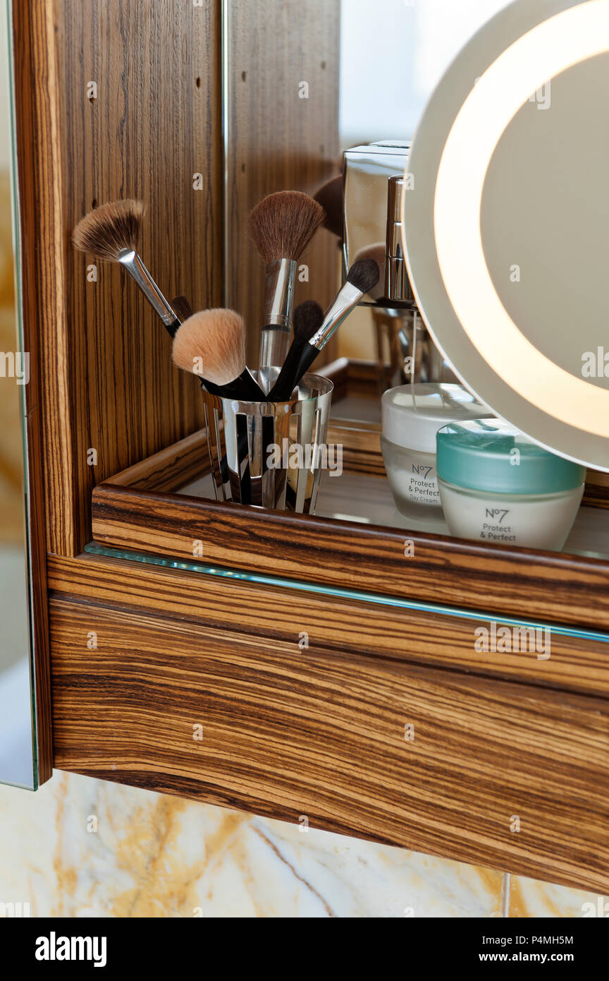 Shaving mirror and make-up brushes in bathroom cupboard - Stock Image